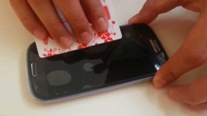 Pemakaian kartu untuk menghilangkan gelembung pada anti gores