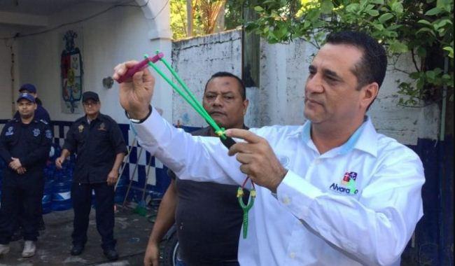 Walikota Alvarado memegang ketapel di hadapan anggota kepolisian