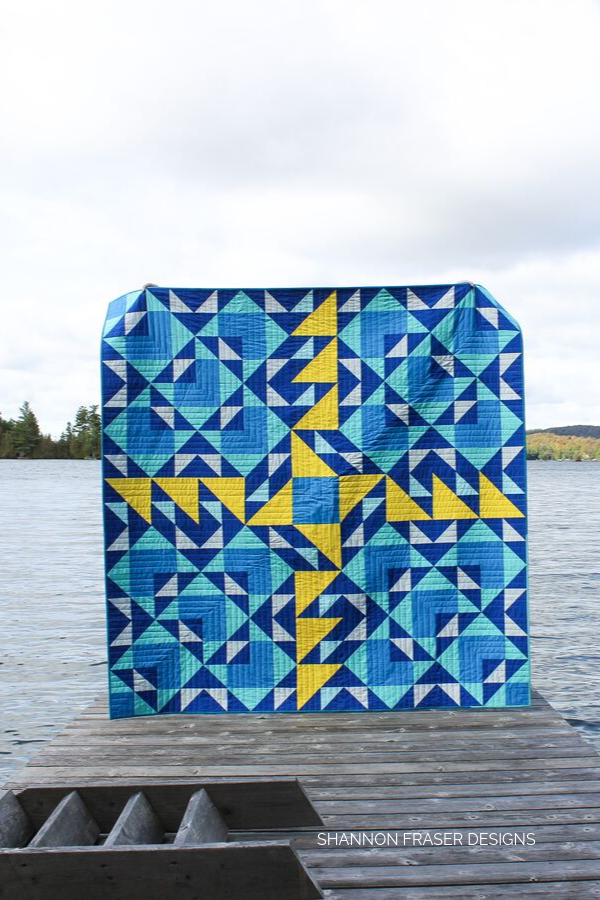 Blue Double Windmill Quilt on the dock | Modern Quilt pattern available in 9 sizes | Shannon Fraser Designs #quiltsinthewild #halfsquaretriangles #bluequilt