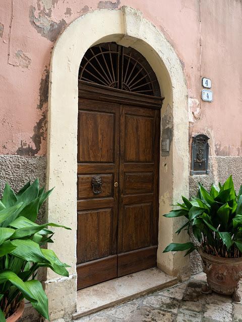 Puerta en Specchia rodeada de plantas con paredes desconchadas