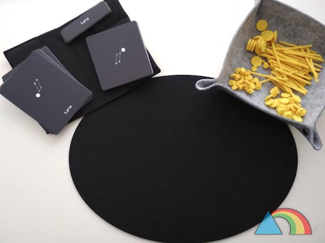 Constructor de constelaciones de la marca Defieltro. Tapete de fieltro negro, bandeja con palitos y círculos de fieltro amarillo y tarjetas de constelaciones de tres partes