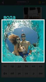 мужчина и женщина делают фотографию сквозь воронку в воде
