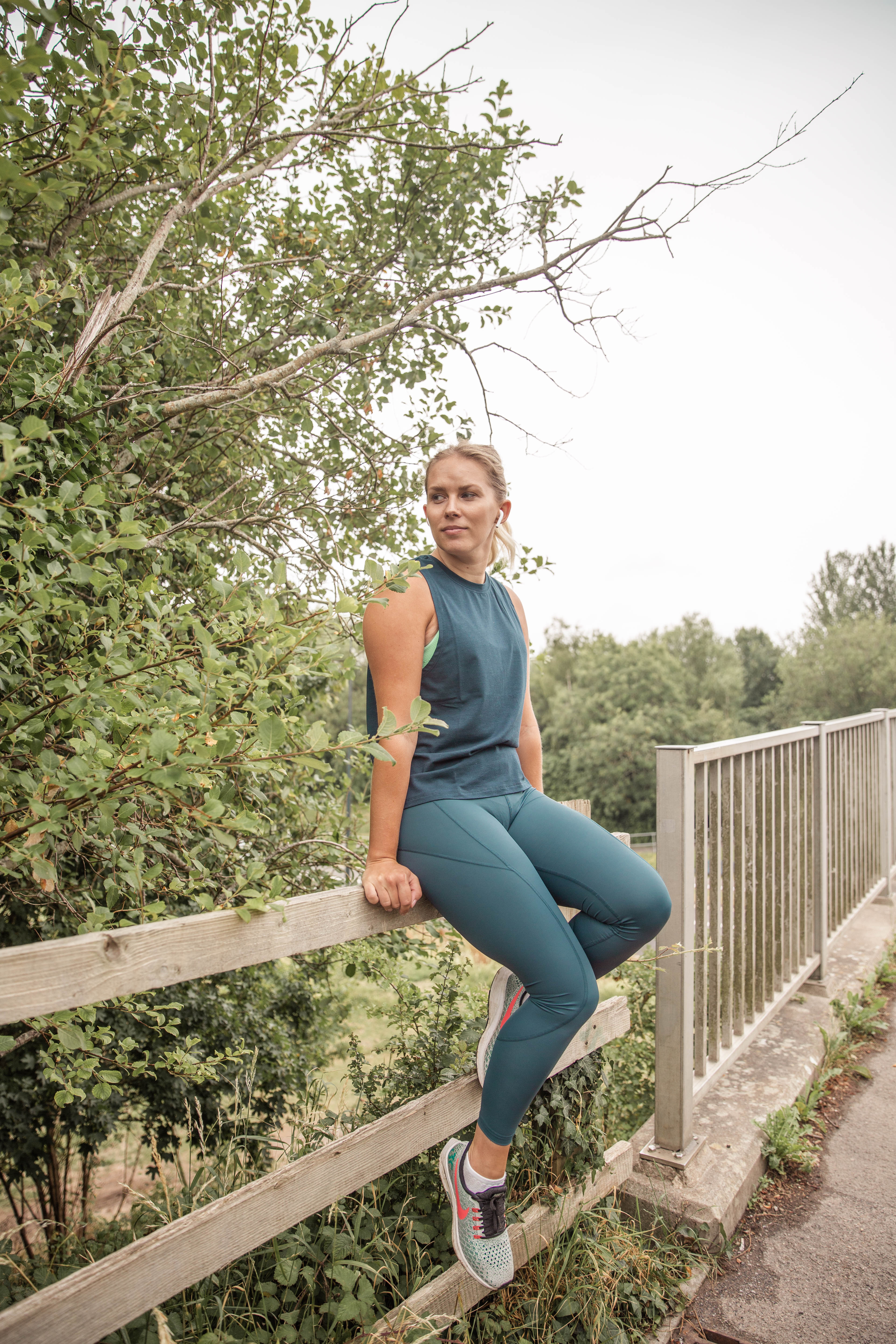 Rachel Emily sat on a fence in matching green running gear