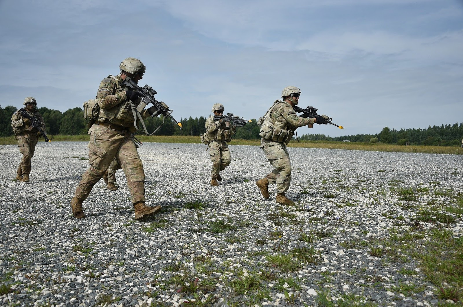 four soldiers tactically move in formation across an open field to illustrate a blog post about re-watchable war movies