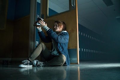 Actress Kathryn Prescott holds a camera in an empty hallway at her school in a movie still for the film Polaroid