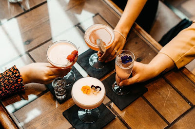 A top down photo of four cocktails, there are hands on the bottom holding each drink