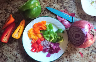 variety of different colored peppers and red onion cut into cubes