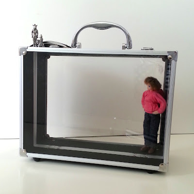 Beauty case with clear sides and a one-twelfth scale modern doll inside. On top of the case are two small metal ornaments.