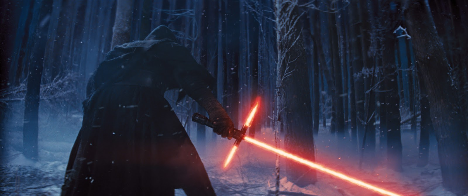 A screen grab from the trailer:  a figure in black stands in a wintery forest.  He weilds a lightsaber, but this one is shaped more like a broadsword, complete with two energy discharges near the base that form a hilt.