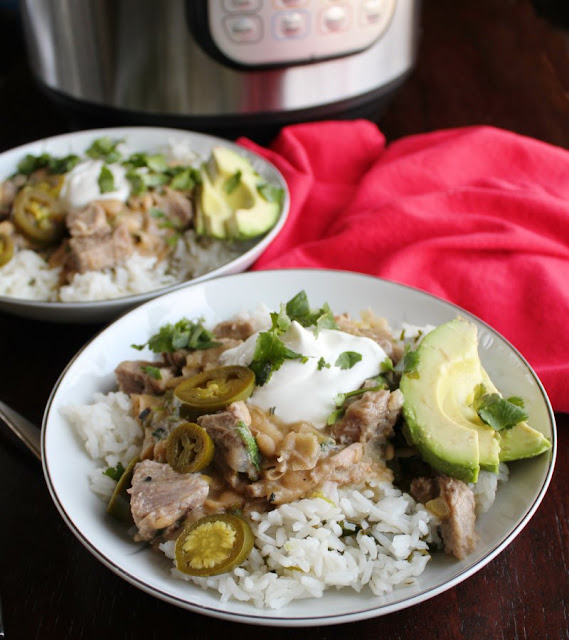 close up of two salsa verde pork burrito bowls with instant pot in background