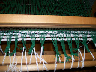 Beating the new weft/woof with the reed.