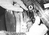 Снять скобу (А) крепления крышки и снять крышку фары.