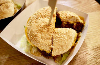 A circular burger with a light brown sesame seed bun cut into quarters in a light white square box on a light wooden table on a light background.