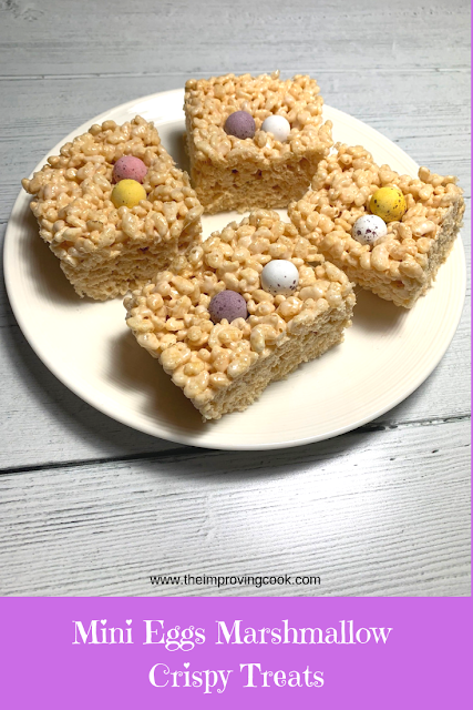 Mini Eggs Marshmallow Crispy Treats on a white plate viewed from the side