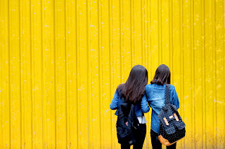 Girls-Stand-With-Denim-Backpacks-in-Front-of-Yellow-Background