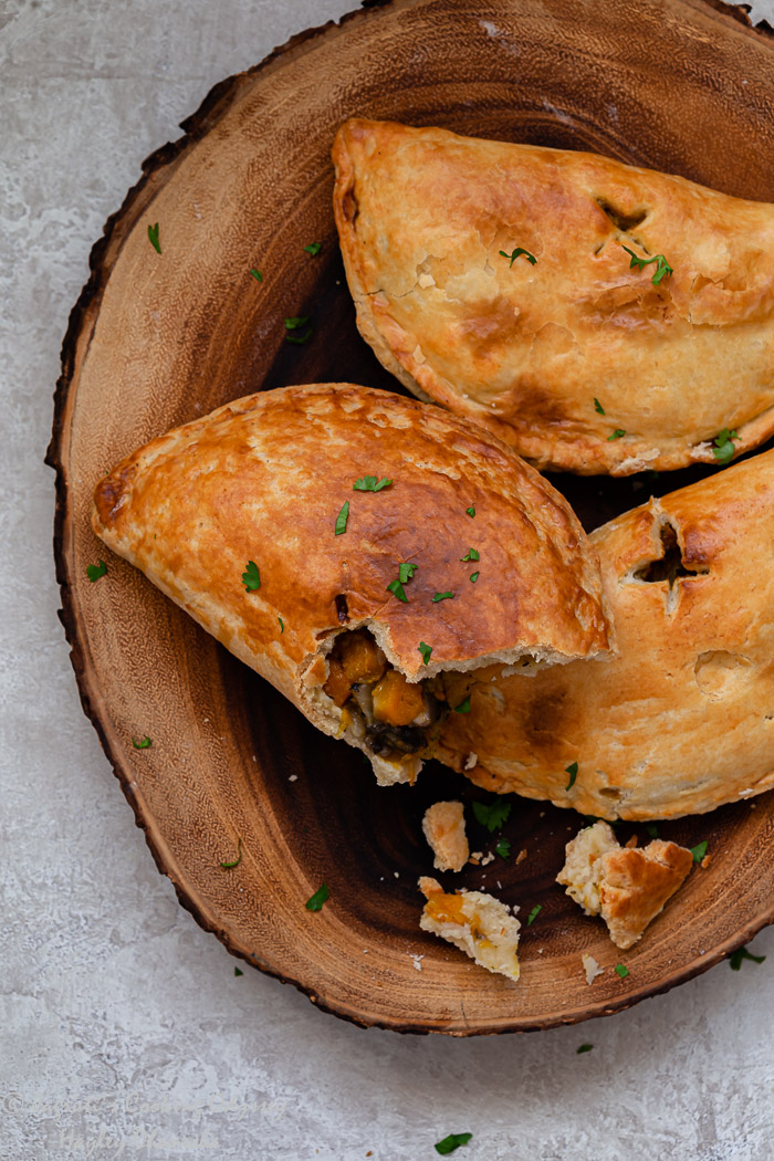 A close up shot of half open vegetable hand pies on a wooden board.