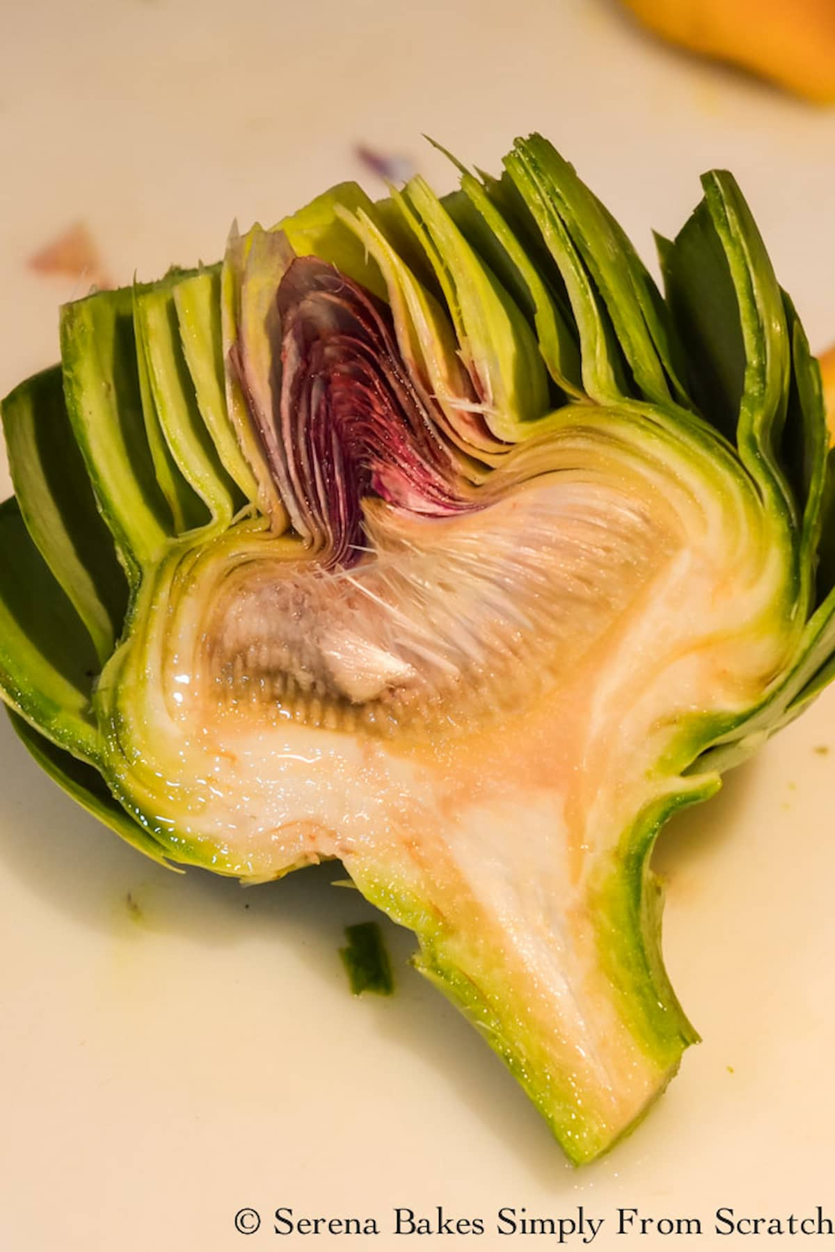 An Artichoke cut in half with the cut side up exposing the fuzzy center.