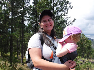 a woman with dark hair and a baseball cap wears a toddler in a pink hat in a gray carrier atop Iron Mountain in South Dakota