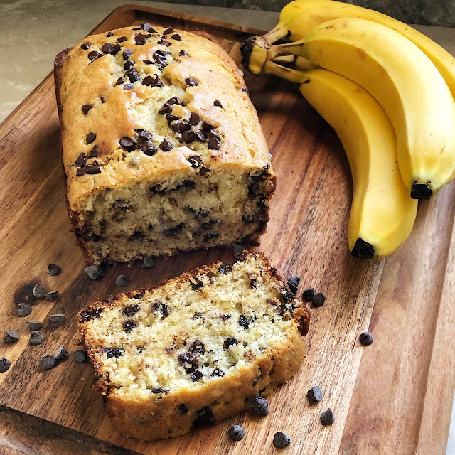 chocolate chip banana bread on a cutting board with bananas