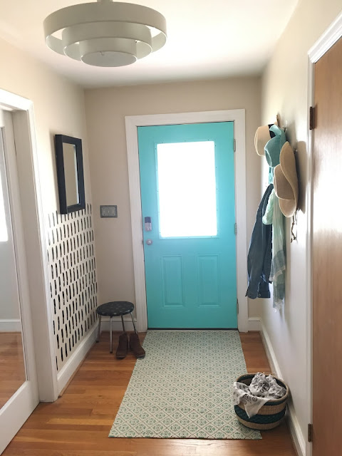 Update a boring entry way with a bright door and hand painted accent wall using a sponge!