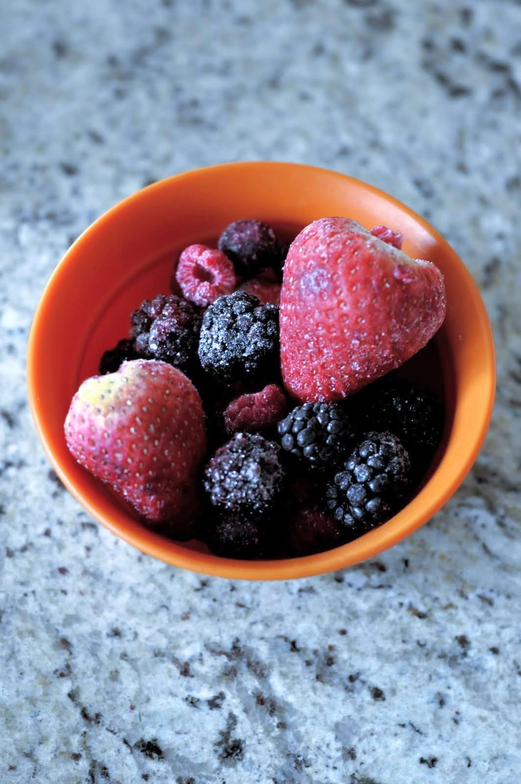 Measuring cup containing a mixture of frozen berries -- strawberries, raspberries, blackberries, and blueberries.