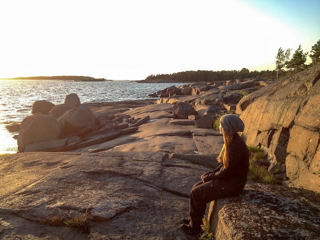 Ihminen istuu kalliontasanteella ja katsoo merelle ilta-auringossa