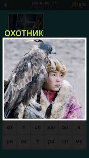 сидит охотник а на руках у него птица для того чтобы поймать добычу