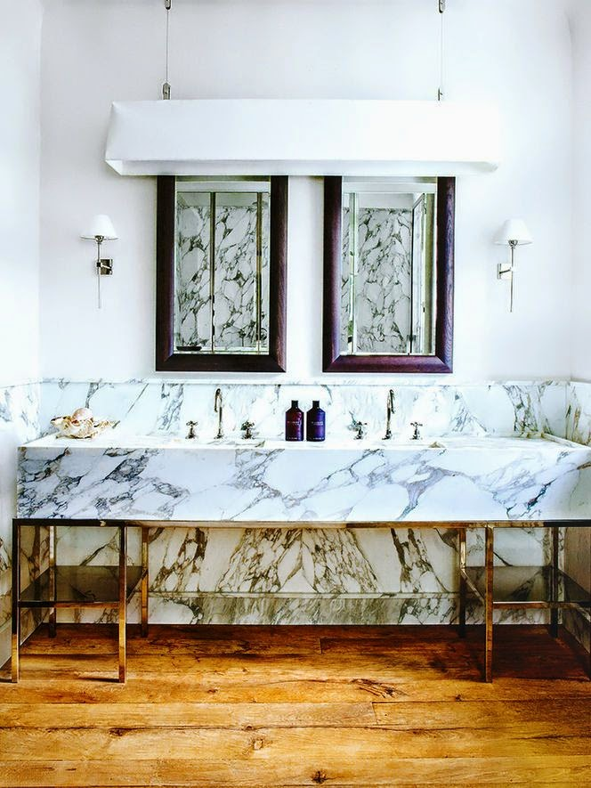 heavily veined marble bathroom with vanitry with chrome legs, wood floor and brown mirrors