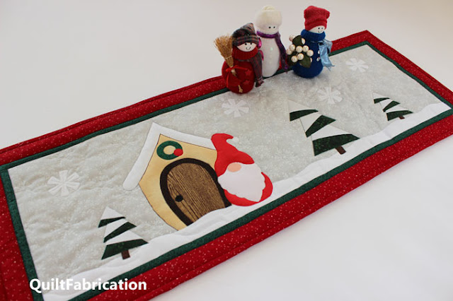 red gnome, beige house, pine trees for a table runner by QuiltFabrication