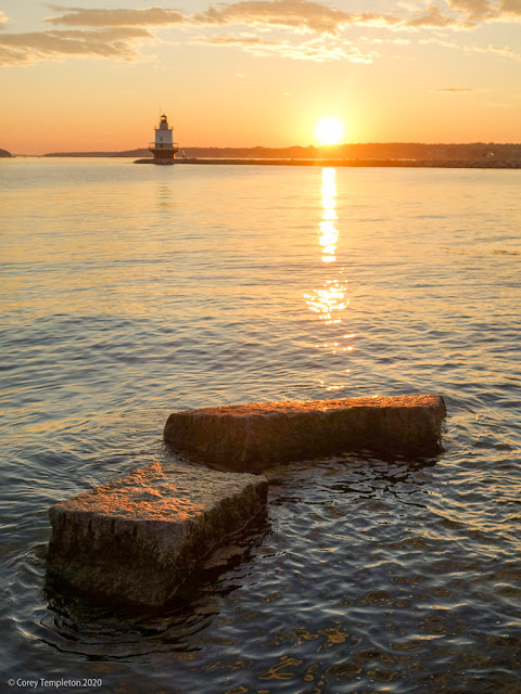 Portland, Maine USA July 2020 photo by Corey Templeton. The sun rising above the rocks at Spring Point this morning.