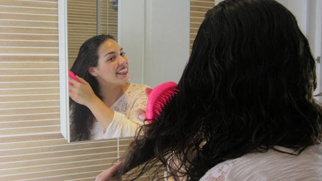 Chica desenredando su cabello frente al espejo