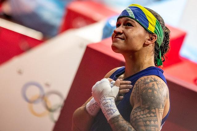 Bia Ferreira olha para o alto. Ela veste uma camisa regata azul e uma bandana estampada com a bandeira do Brasil na cabeça