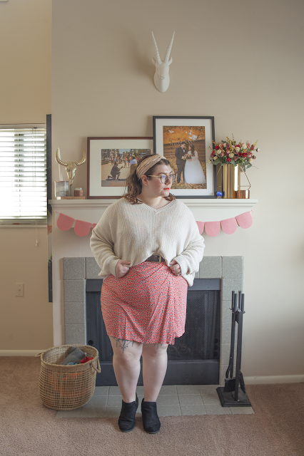 An outfit consisting of a pink lace scarf tied in hair, white sweater belted over pink and orange dotted wrap dress and black booties.