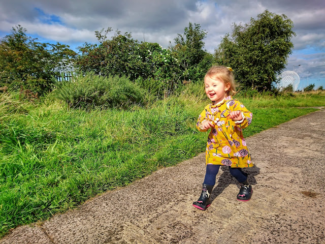 A small girl with blonde hair half tied up smiling, wearing a mustard dress with pink and white dandelion flowers printed on, paired with navy tight and navy Wellington boots fearing horses in pink and white. She is walking along a pathway with bushes and trees. The sky is blue seen peeping through grey clouds.