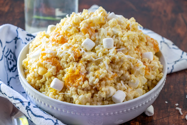 White bowl filled with fruity pasta salad with oranges, pineapples, coconut, and marshmallows