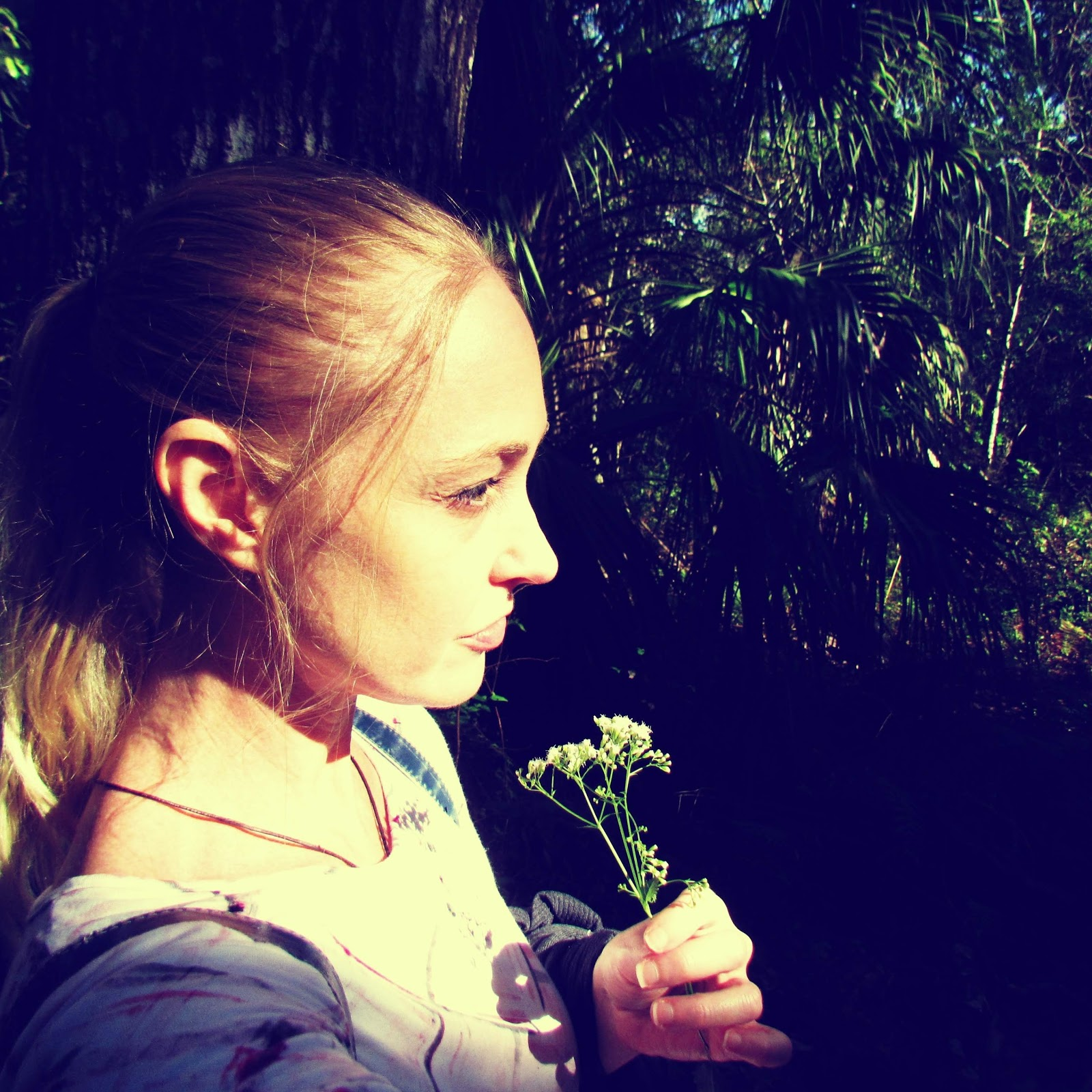 Self-portrait of a blonde woman holding a flower while hiking in an enchanted forest in Florida