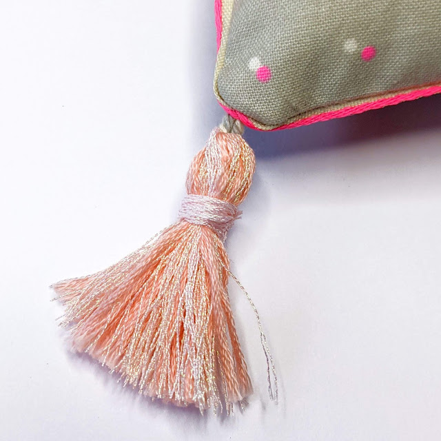 close up detail of corner tassel made of metallic and standard embroidery floss and also showing ribbon edge detail on the pillow