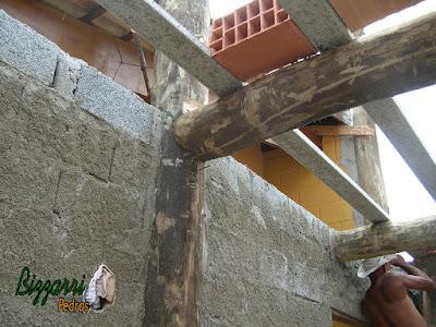 Detalhe da armação da lage em cima das vigas de madeira de eucalipto tratado com os pilares de madeira com a alvenaria de bloco de cimento.