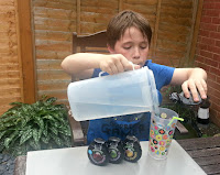 Boy sitting in garden making Robinsons squash