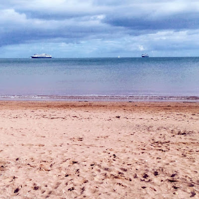 red sand foreground, blue water and blue sky. 2 large ships and a small sailing boat