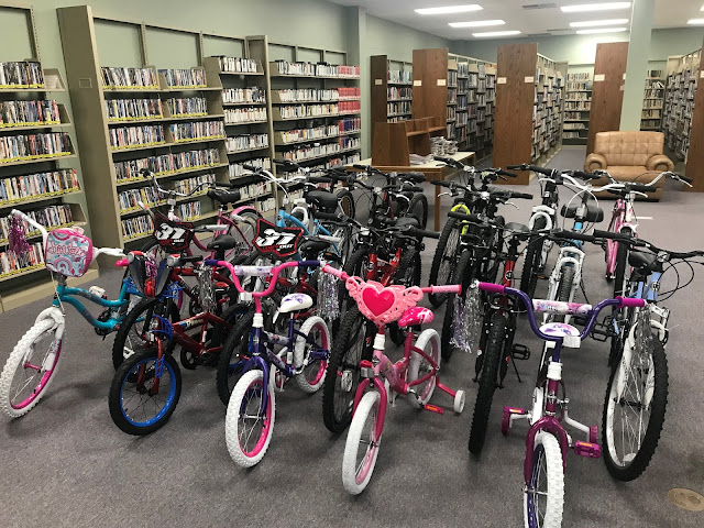 A collection of about twenty bicycles sits in the middle of a library.
