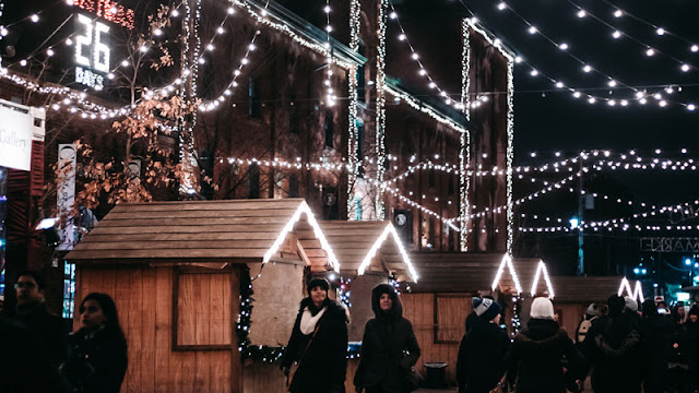 two women walking beneath Christmas lights