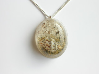 Oval necklace pendant containing ashes and a seashell