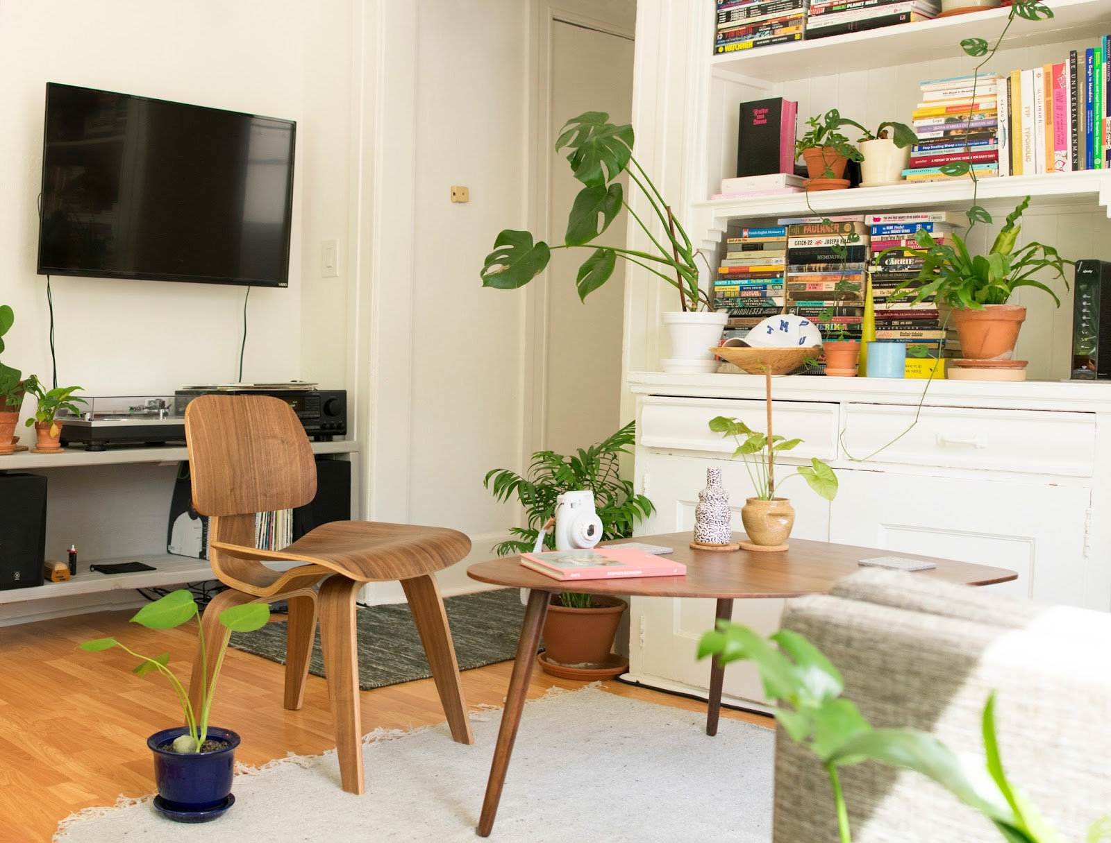 a living room with plants scatter around. There is a record player in the background with some wooden chairs around a coffee table.