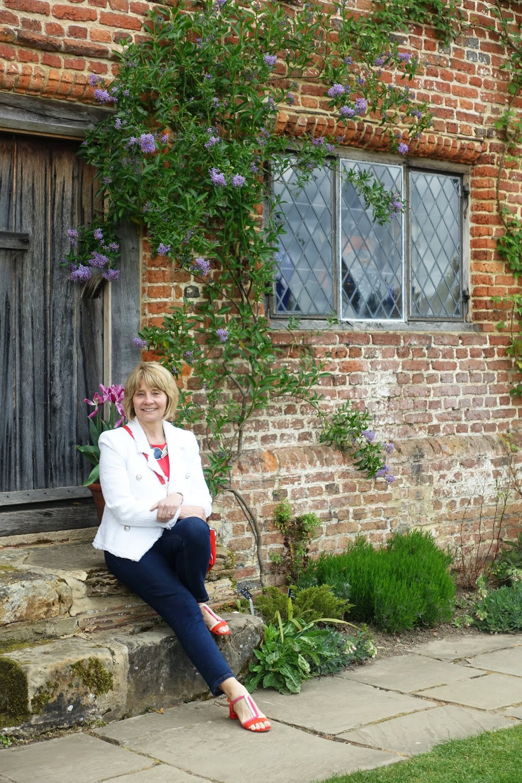 Over 50s blogger Gail Hanlon seated on the steps of an outbuilding with diamond pane windows at Sissinghurst Castle garden in Kent