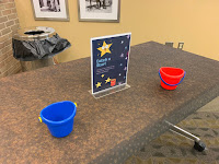 "table with two small buckets and ""Catch a Star"" sign"