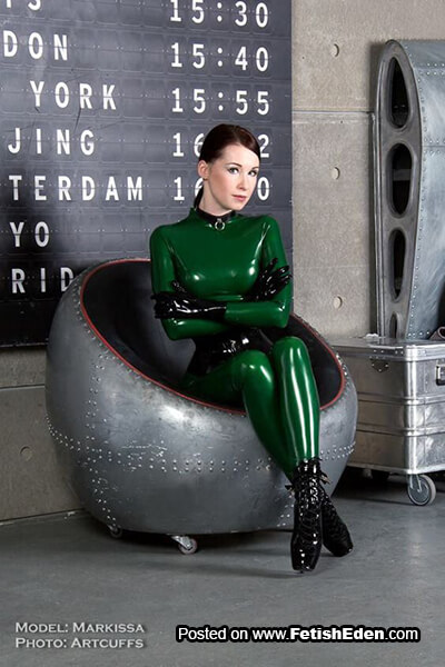 Markissa wears green latex catsuit, short black latex gloves and black balet boots