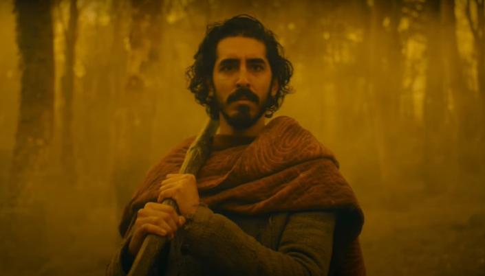 Imagem: o personagem Gawain, interpretado por Dev Patel, um homem de pele escura com longos cabelos e barba pretos, em roupas medievais, com um tipo de casaco de lã e uma capa vermelha sobre os ombros, segurando o cabo de um longo machado, enquanto anda através de um bosque iluminado pela cor amarelada.
