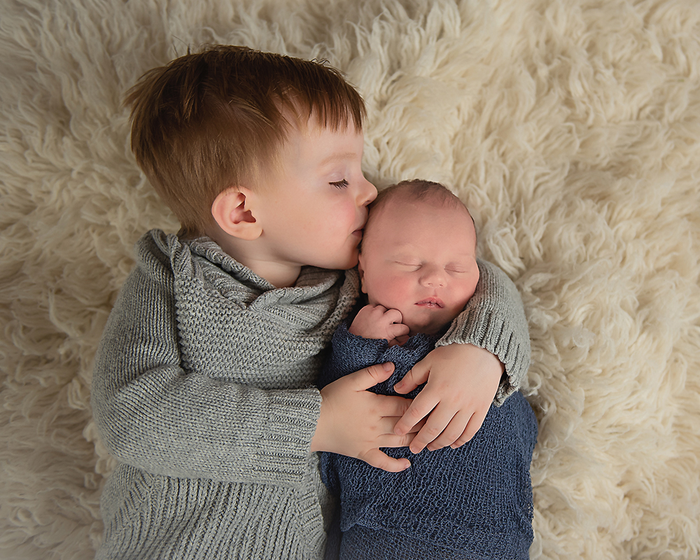 newborn baby boy with sibling big brother in blue and gray on a cream rug