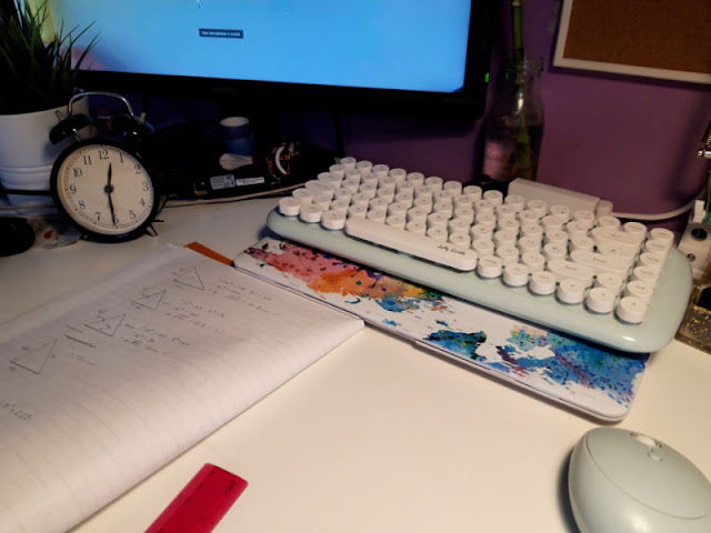 A desk set up for home school working.  There is an online maths lesson in progress on the computer